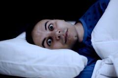 Stående av en sömnlös man i hans säng Arkivfoto