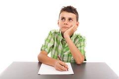 Stående av en schoolboy som gör hans läxa Arkivfoto