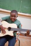 Stående av en schoolboy som leker gitarren royaltyfri fotografi