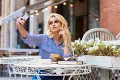 Stående av en självstående för ung attraktiv blond damdanande med hennes digitala kamera för smartphone Arkivbild