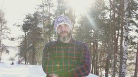 Stående av en skäggig le man i en vinterskog som korsar hans armar arkivfilmer