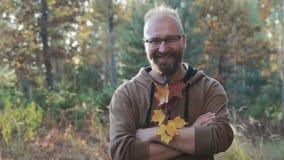 Stående av en skallig man med exponeringsglas och ett skägg, som jublar mot höstskogen stock video