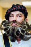 Stående av en skotteman med ett lockigt stort härligt skägg Ett tokigt skägg från en frisersalong arkivfoto