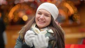 Stående av en skratta flicka som in bär en vit hatt- och Grey Mitts Over Christmas Lights bakgrund, kvinnavärmehänder lager videofilmer
