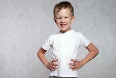 Stående av en skratta pojke på en grå bakgrund Royaltyfria Bilder