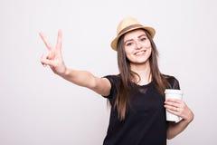 Stående av en skratta ung flicka i mobiltelefon och kopp kaffe för hatt hållande på en grå färg Arkivfoto