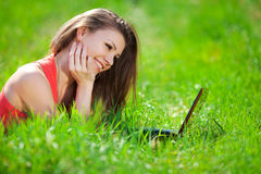 Stående av en smart ung kvinna som ligger på gräs och använder bärbara datorn Fotografering för Bildbyråer