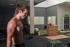 Stående av en stark ung man som ler att vila i idrottshallen royaltyfri foto