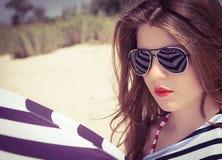 Stående av en stilfull flicka i en randig t-skjorta och solglasögon Royaltyfri Bild