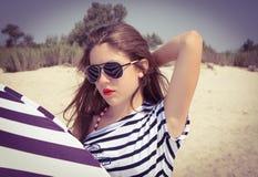 Stående av en stilfull flicka i en randig t-skjorta och solglasögon b Royaltyfri Fotografi