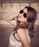 Stående av en stilfull flicka med solglasögon i staden Arkivbilder