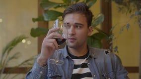 Stående av en stilig grabb som dricker vin som sitter på en tabell i en restaurang Ung man som tycker om en drink, medan vänta arkivfilmer