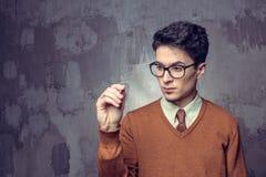 Stående av en stilig handstil för ung man något på en glass writeboard fotografering för bildbyråer