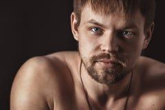 Stående av en stilig man på en svart bakgrund Manlig framsidacloseup Royaltyfria Bilder