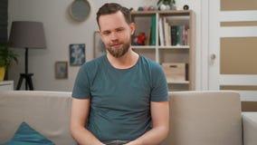 St?ende av en stilig man som sitter p? en soffa p? vardagsrum som ser kameran Leende f?r ung man lyckligt och att sitta p? soffan arkivfilmer