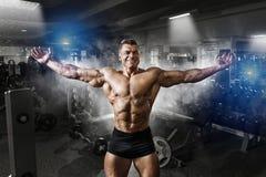 Stående av en stilig muskulös kroppsbyggare som poserar i idrottshall arkivfoton