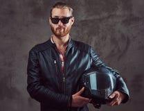 Stående av en stilig stilfull rödhårig mancyklist i ett svart läderomslag och solglasögon, hållmotorcykelhjälm som poserar arkivfoton