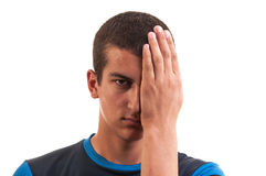 Stående av en stilig tonåring som täcker ett öga med den vänstra handen Arkivfoto