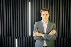Stående av en stilig ung man i en affärsdräkt med korsade händer mot den trämörka väggen i modernt kontor Royaltyfri Bild