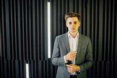 Stående av en stilig ung man i en affärsdräkt mot den trämörka väggen i modernt kontor Arkivbilder
