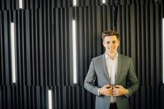 Stående av en stilig ung man i en affärsdräkt mot den trämörka väggen i modernt kontor Arkivbild