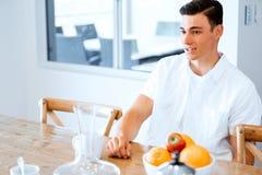 Stående av en stilig ung man i köket arkivbilder