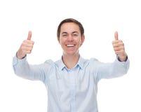 Stående av en stilig ung man som ler med tummar upp i beröm Arkivbilder