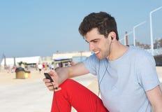 Stående av en stilig ung man som utomhus lyssnar på spelaren mp3 Arkivfoto