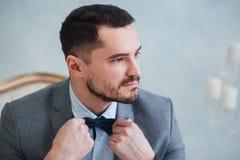 Stående av en stilig vuxen man i en grå dräkt i studion Brudgummen väntar på bruden Royaltyfri Fotografi