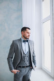 Stående av en stilig vuxen man i en grå dräkt i studion Brudgummen väntar på bruden Arkivbilder