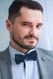 Stående av en stilig vuxen man i en grå dräkt i studion Brudgummen väntar på bruden Royaltyfri Bild