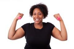 Stående av en svart fettig kvinna som utarbetar med fria vikter - Arkivfoton