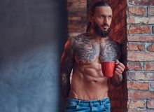 Stående av en tattoed shirtless man med en stilfullt frisyr och skägg, drinkmorgonkaffe som lutar mot en tegelsten royaltyfria bilder