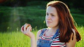 Stående av en tonårs- flicka Äter ett stort rött äpple på en grön äng stock video