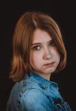 Stående av en tonårs- flicka på en svart bakgrund arkivbild