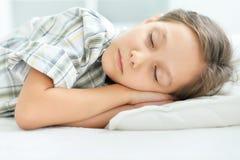 Stående av en trött liten flicka som sover i säng royaltyfria bilder