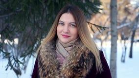 Stående av en trendig sexig härlig flicka i bakgrunden av en vinterskog lager videofilmer