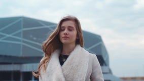 Stående av en trevlig nätt blond kvinna som går långsamt i väg från en modern stadsbyggnad efter arbete i den blåsiga aftonen lager videofilmer