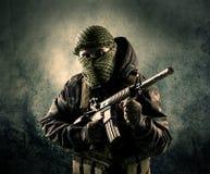 Stående av en tungt beväpnad maskerad soldat med grungy backgroun Royaltyfri Foto