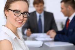 Stående av en ung affärskvinna mot en grupp av affärsfolk på ett möte arkivbilder