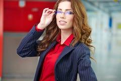Stående av en ung affärskvinna som ler, i en kontorsen Arkivbild