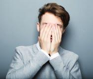 Stående av en ung affärsman som är rädd och som är förskräckt av något arkivfoton