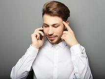 Stående av en ung affärsman som talar på telefonen fotografering för bildbyråer