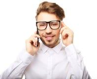 Stående av en ung affärsman som talar på telefonen arkivbild