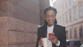 Stående av en ung afrikansk amerikanaffärskvinna i en dräkt och att stå på gatabakgrunden som dricker kaffe och stock video