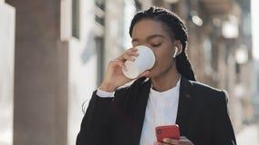 Stående av en ung afrikansk amerikanaffärskvinna i en dräkt som står på den gamla stadsbakgrunden som dricker kaffe och lager videofilmer