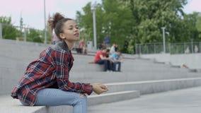 Stående av en ung afrikansk amerikankvinna som bär rutigt skjortasammanträde på tegelstentrappa, utomhus lager videofilmer
