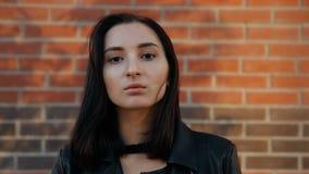 Stående av en ung allvarlig sexig kvinna mot en tegelstenvägg Ultrarapidskott arkivfilmer