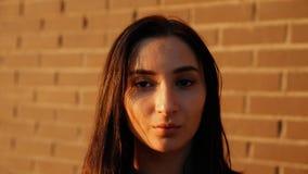 Stående av en ung allvarlig sexig kvinna mot en tegelstenvägg Ultrarapidskott stock video