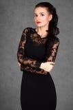 Stående av en ung attraktiv kvinna i en svart aftonklänning Fotografering för Bildbyråer